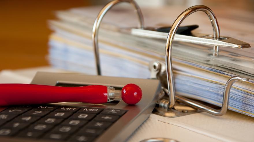 Archivador, calculadora y boli rojo