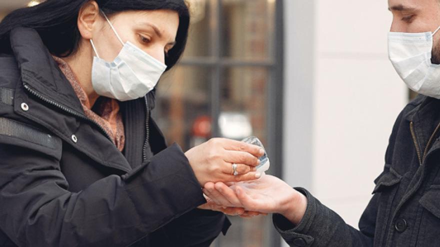Imagen de cabecera que muestra a dos personas con mascarillas y desinfectándose las manos