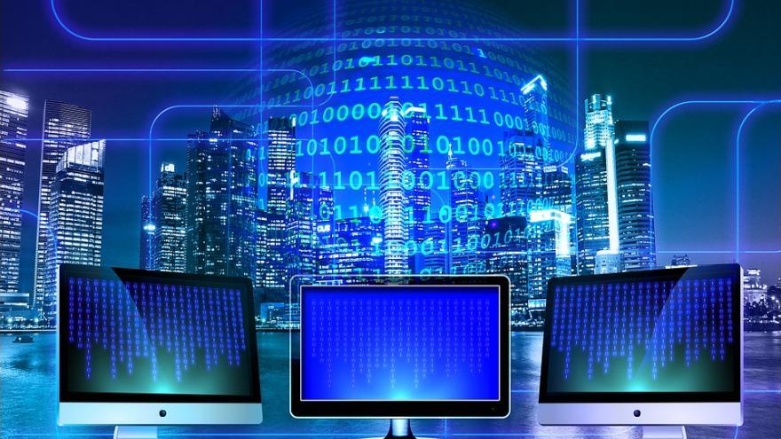 Imagen con tres ordenadores en primer plano y fondo azul con dígitos binarios