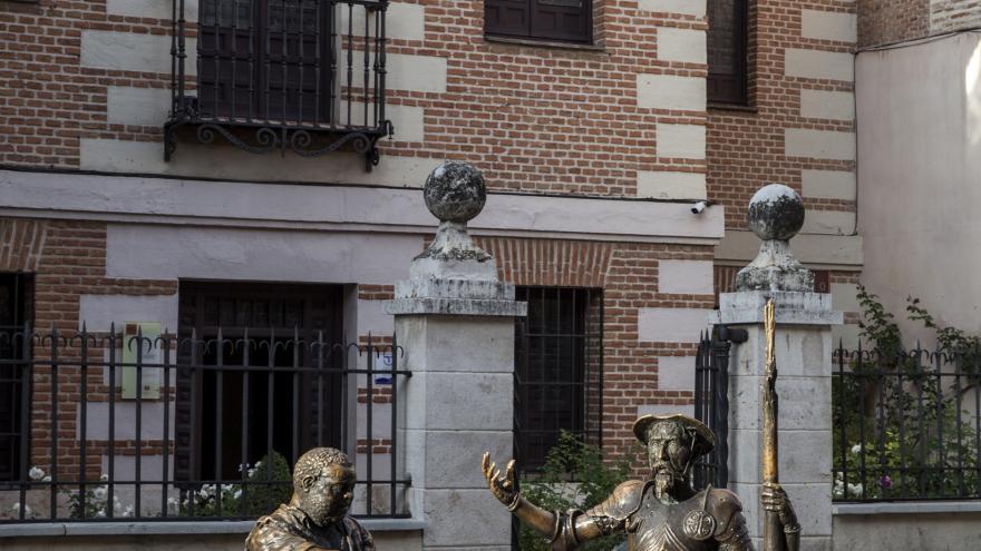 Estatuas en bronce de don Quijote y Sancho sentados en un banco frente a la fachada principal del Museo Cervantes en Alcalá de Henares