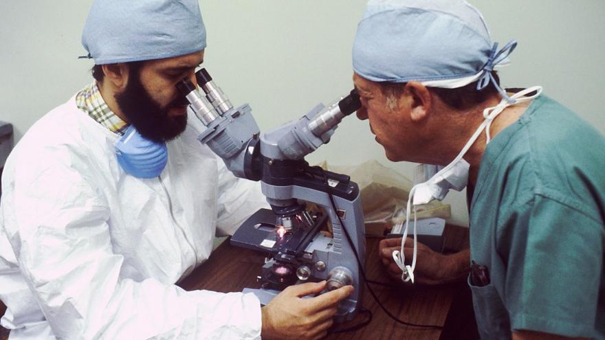 Dos médicos miran por dos visores del mismo microscopio
