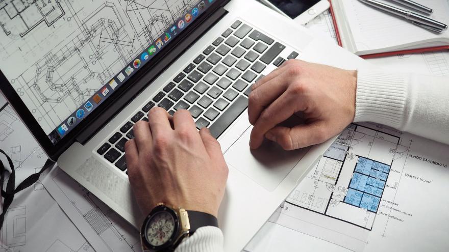 manos de hombre trabajando con ordenador y documentos