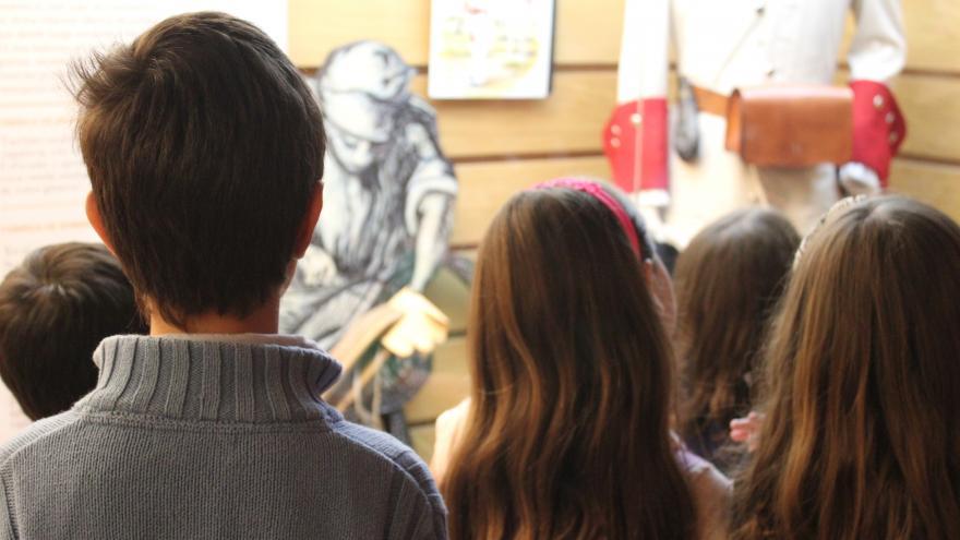 Niños y niñas observando al vitrina sobre textiles y uniformes en el Centro de Interpretación de Nuevo Baztán
