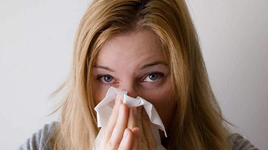 Mujer limpiándose la nariz con un pañuelo