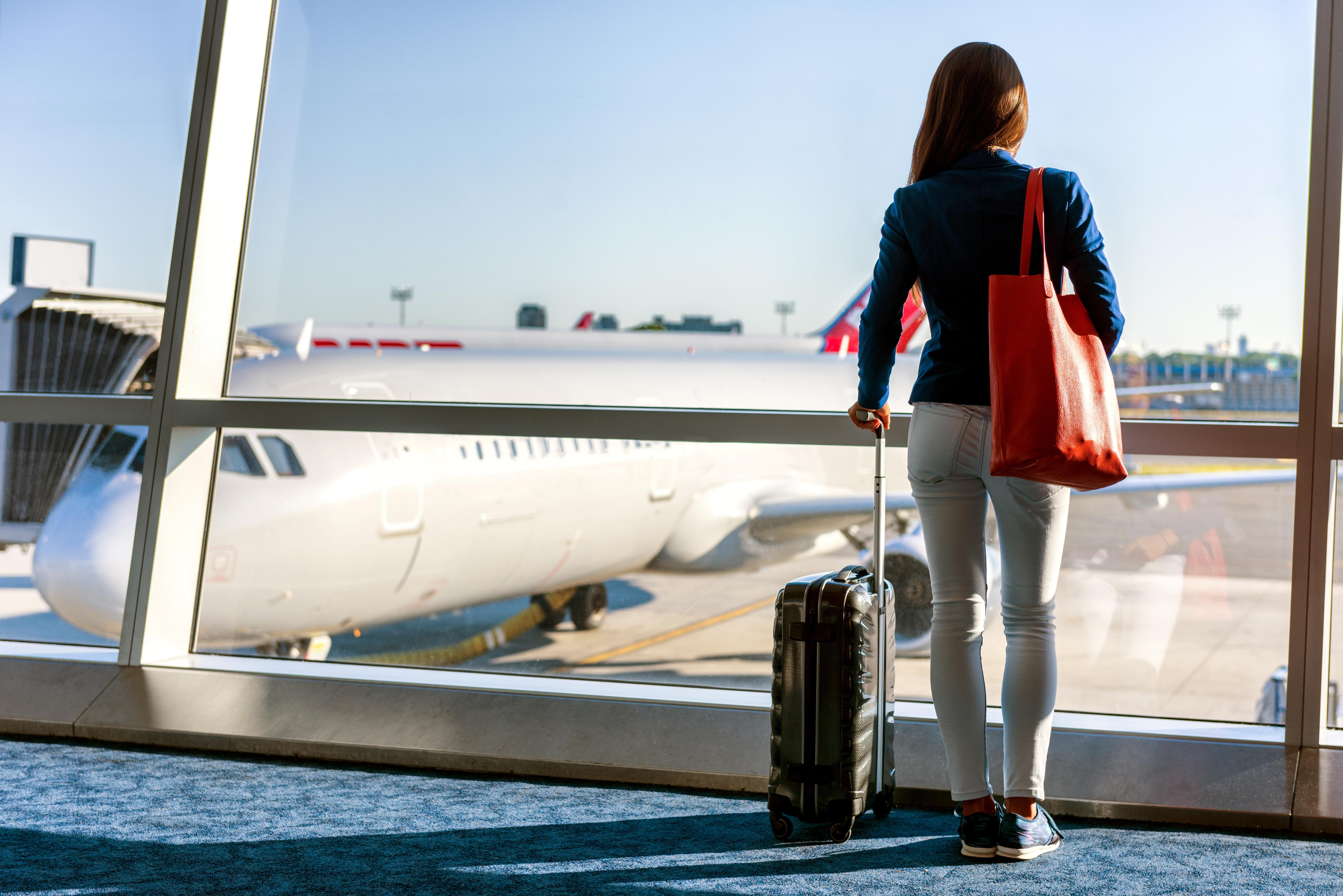 Mujer de espaldas, con una maleta y un bolso, mirando desde la terminal a un avión aparcado