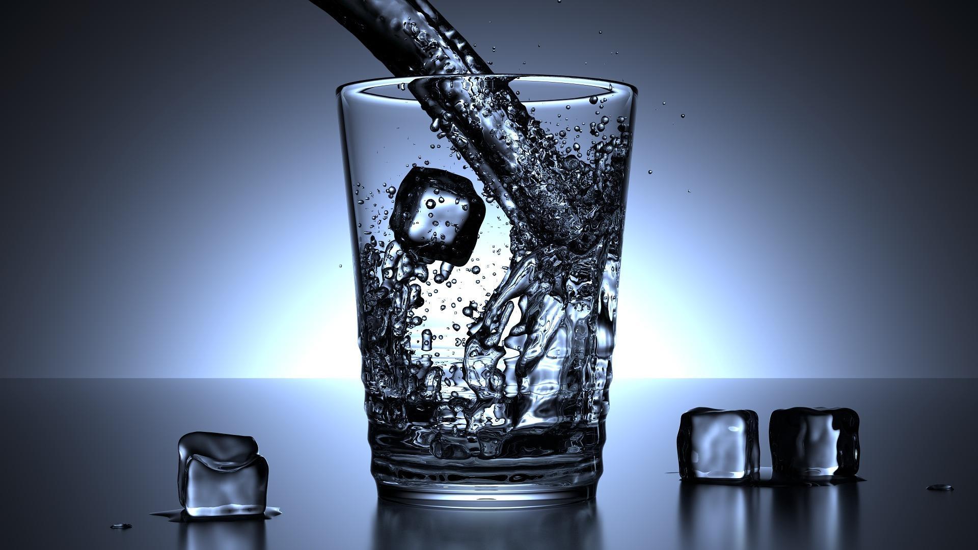 Imagen a contraluz de un vaso de agua y unos cubitos de hielo en una mesa