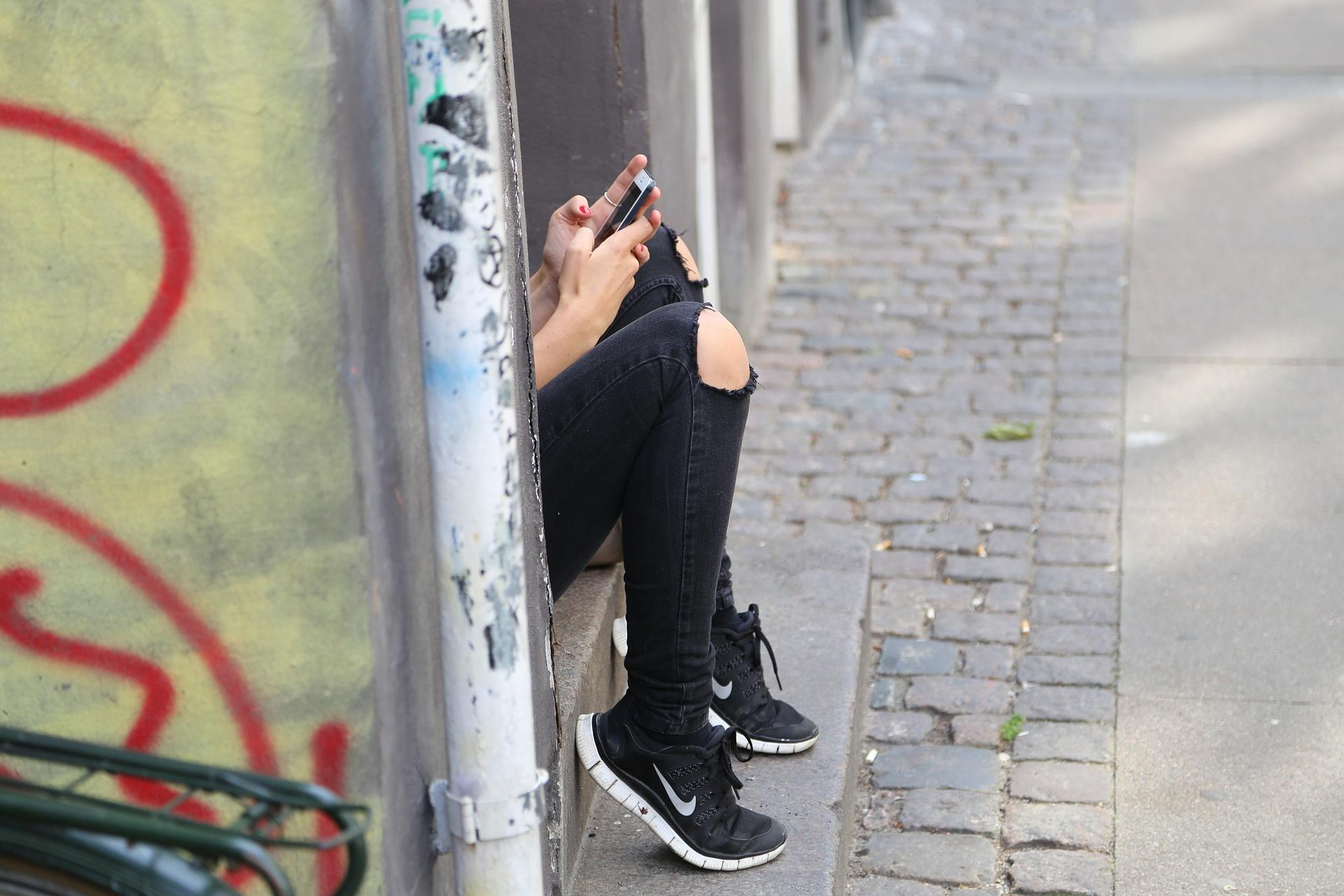 Chica sentada con móvil