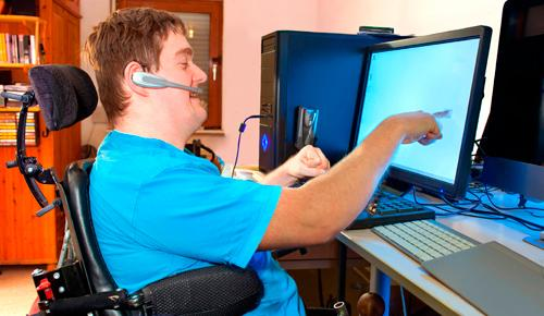 Hombre joven con parálisis cerebral trabajando en un ordenador