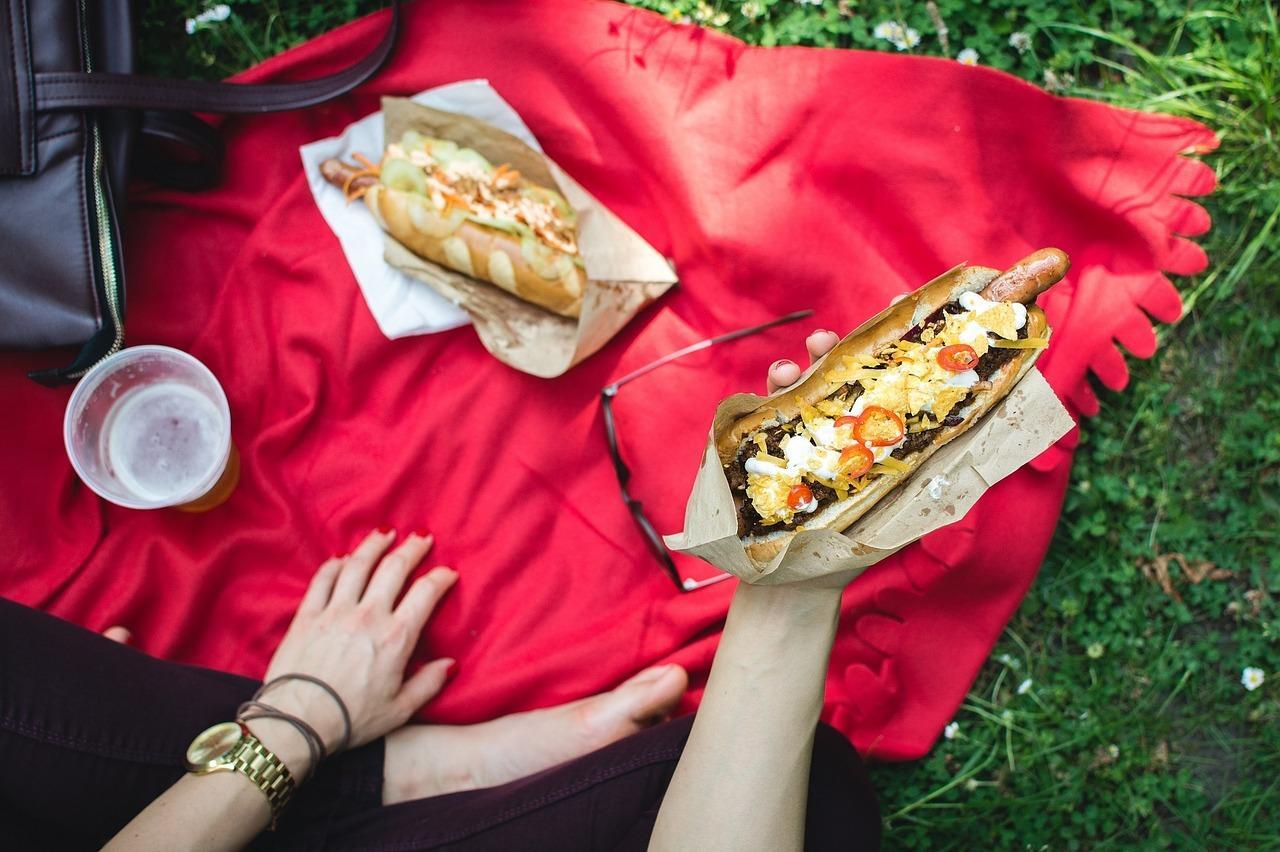 Picnic en la hierba sobre mantel rojo y mano agarrando un perrito caliente