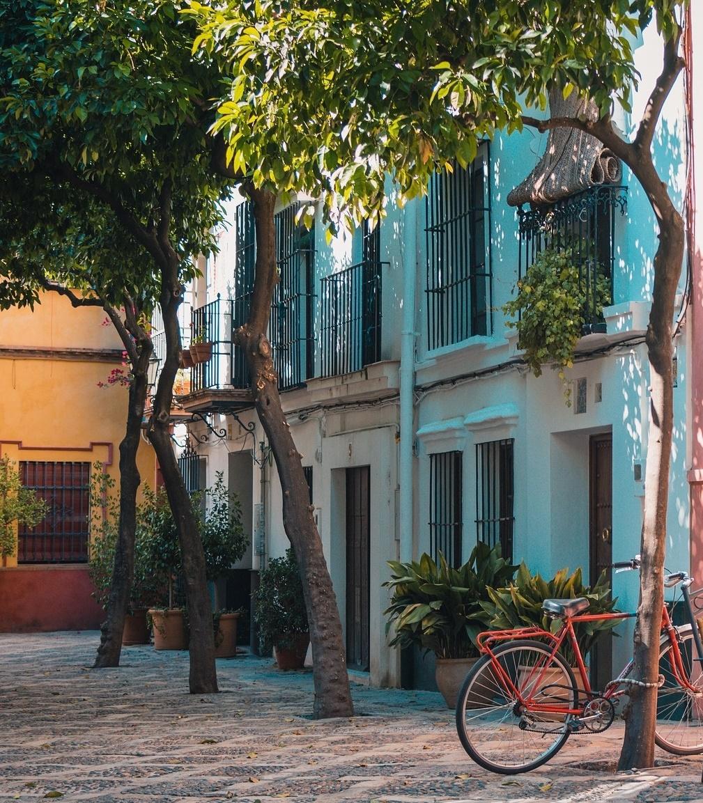 Fachada de un edificio en una calle con árboles y bicicleta roja