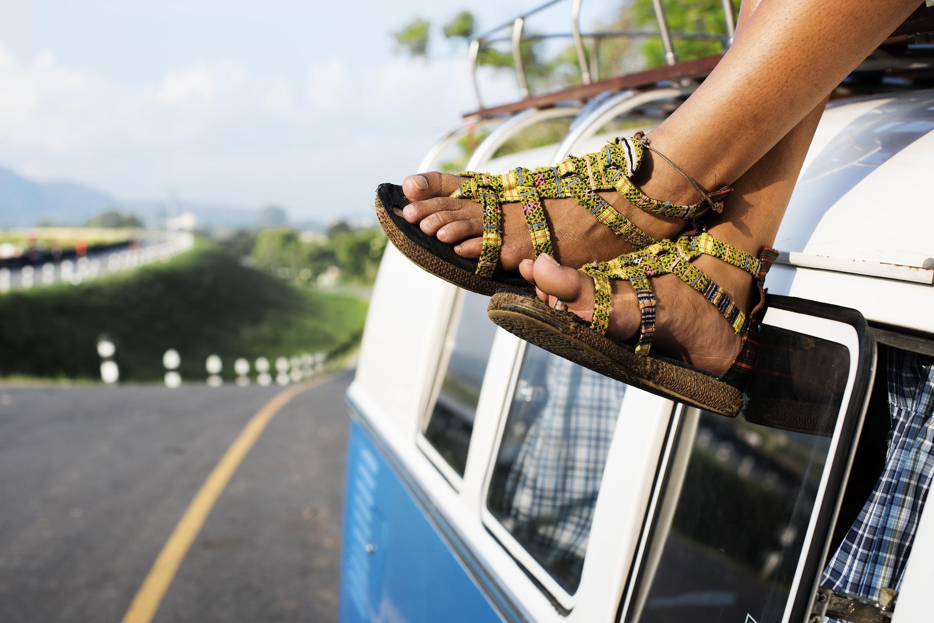 Pies con sandalias encima de un coche