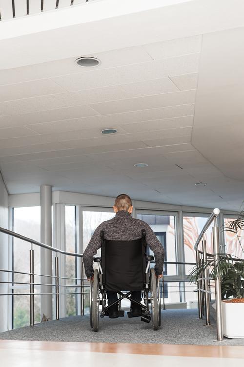 Persona usuaria de silla de ruedas accediendo a un edificio
