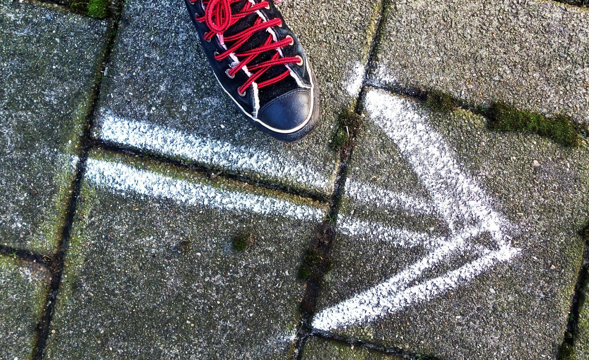 Flecha dibujada con tiza sobre el asfato