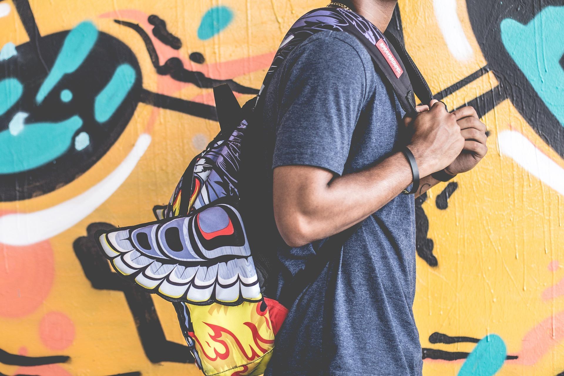 Chico con mochila a la espalda pasando por una pared con graffiti