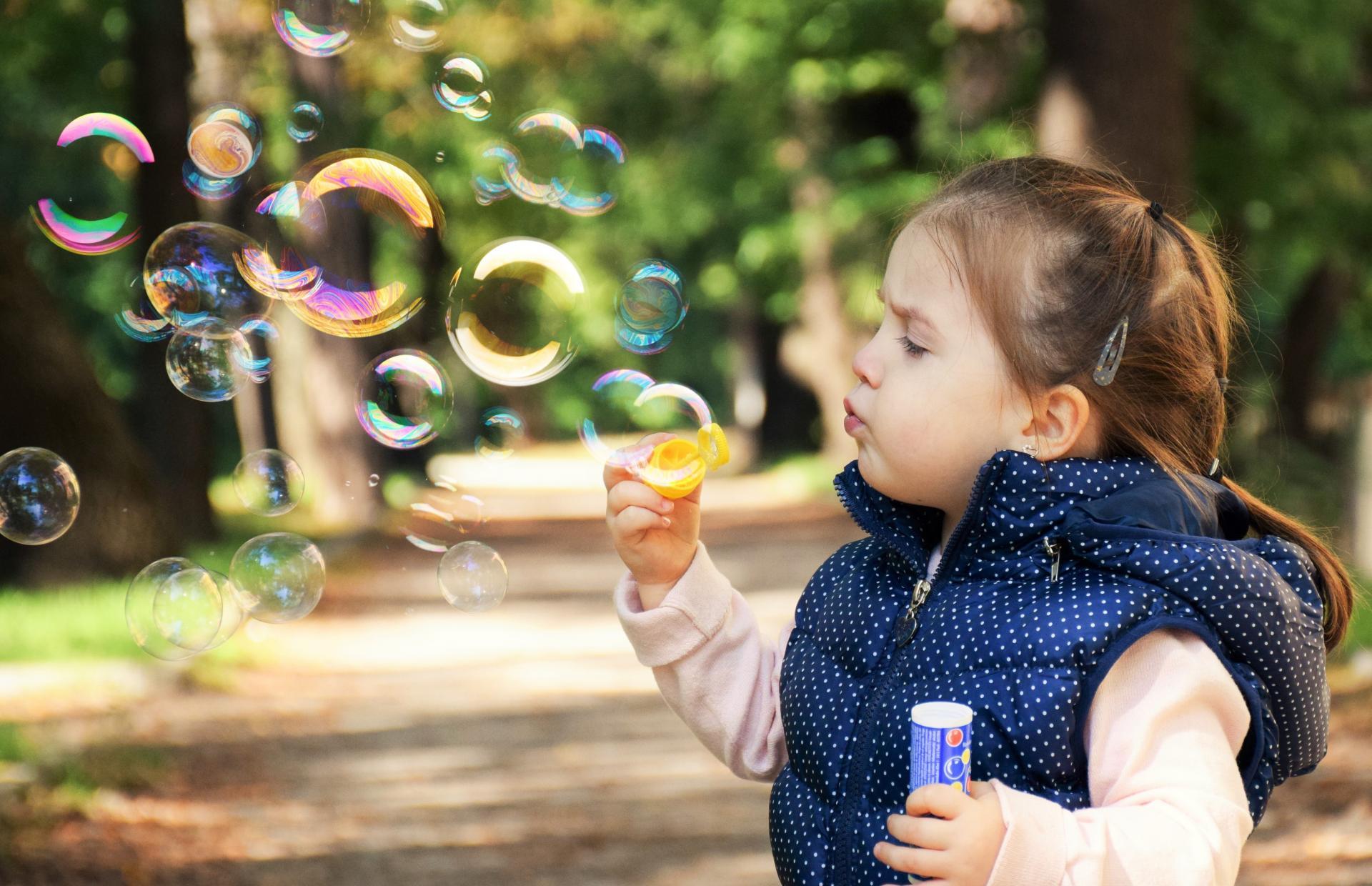 Niña con juguete de burbujas