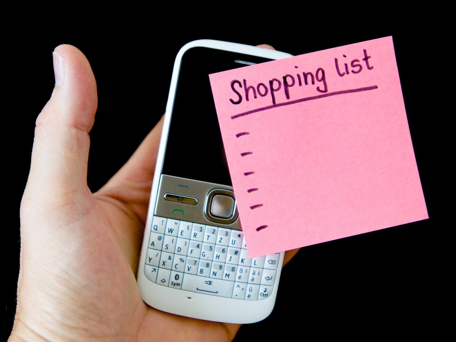 Mano sujetando un móvil con un post-it con la lista de la compra