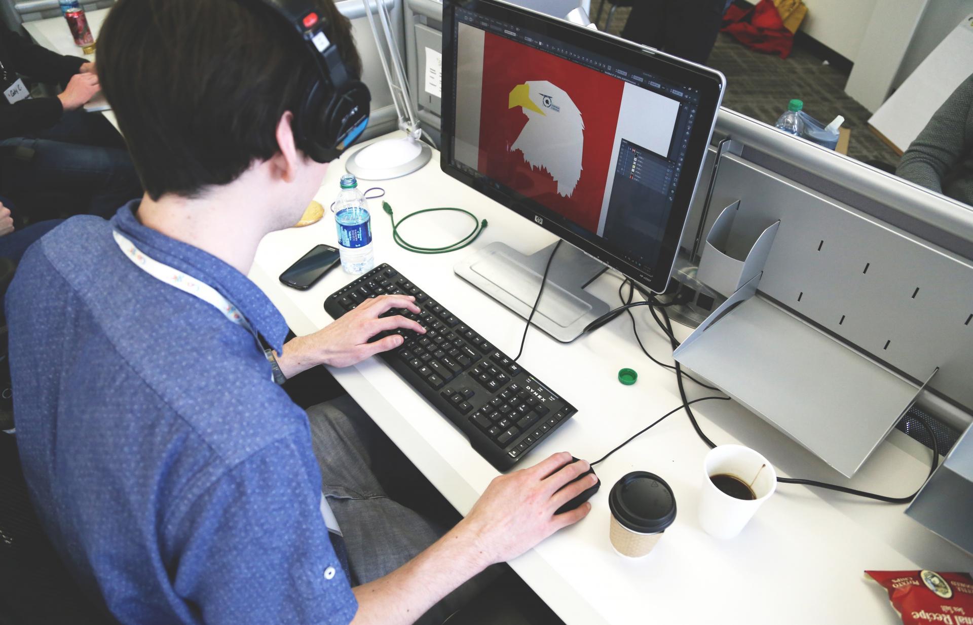 Chico con cascos escribiendo en ordenador portatil