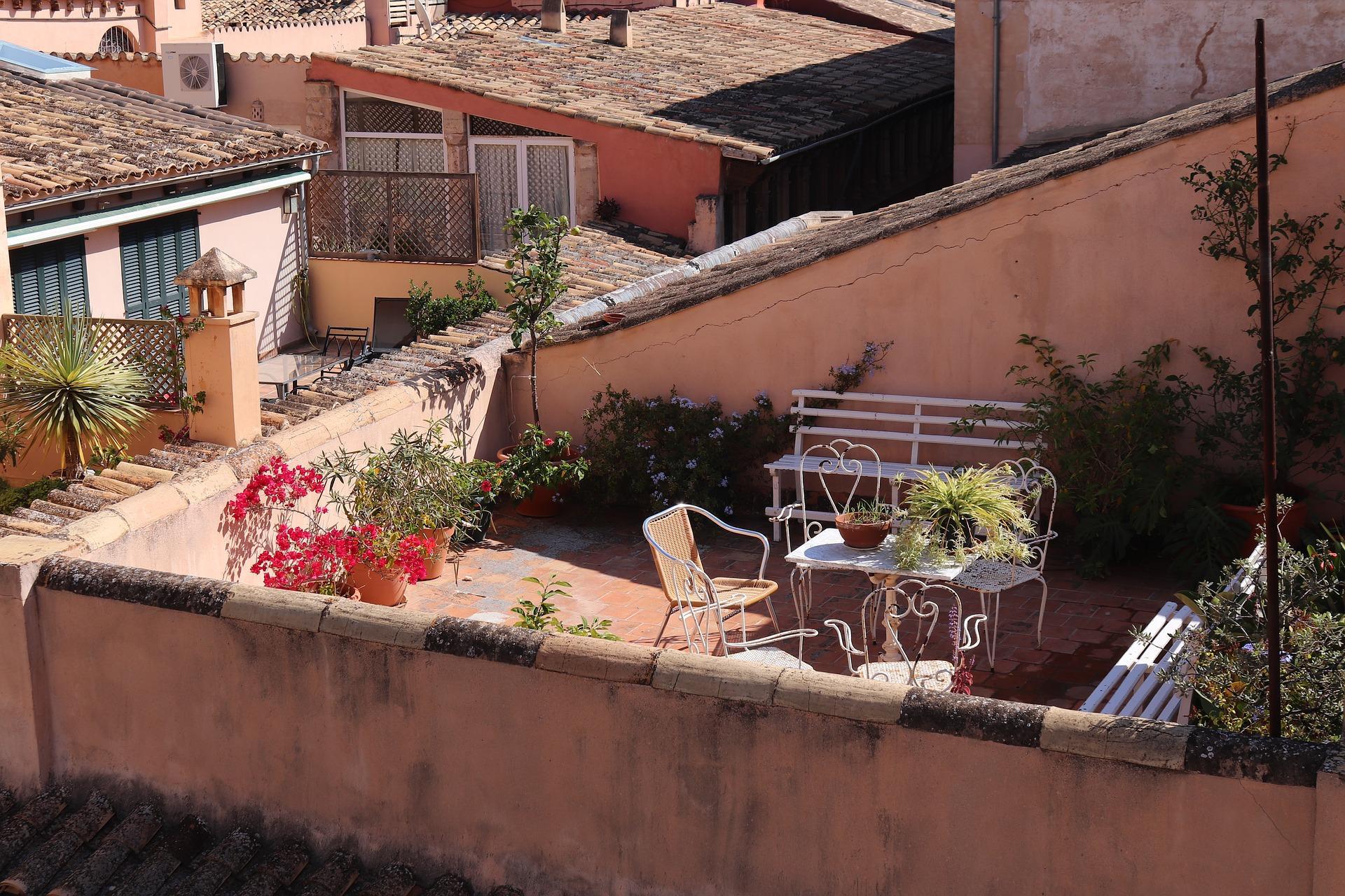 Terraza de un edificio con mesa sillas y flores