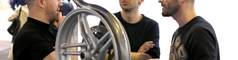 Tres hombres en una feria de arte contemporáneo hablando tras una escultura hecha con ruedas plateadas y doradas de vehículos