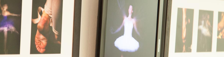 Fotografías y audiovisual de bailarines y bailarinas de ballet clásico, dispuestas en fila en una pared
