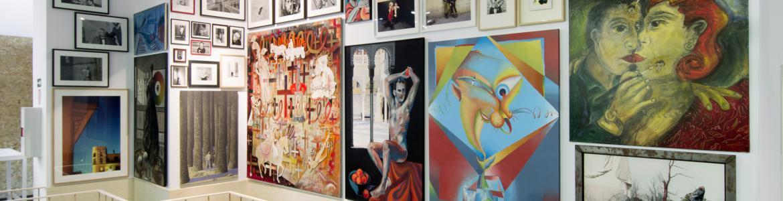 Pared llena de cuadros dispuestos en varias alturas y con temáticas variadas sin orden aparente