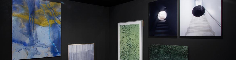 Vista de una exposición con paredes oscuras y varios lienzos colgados en ellas