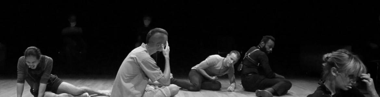 imagen en la que se ve a 5 integrantes de la compañía en el escenario sentados con gestos de dolor