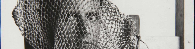 Fotografía en blanco y negro de una cabeza de hombre dentro de una red de pesca