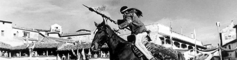 Indio a caballo saltando por encima de un carruaje volcado en el suelo