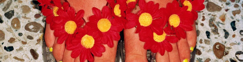 Pies femeninos con chanclas decoradas con flores