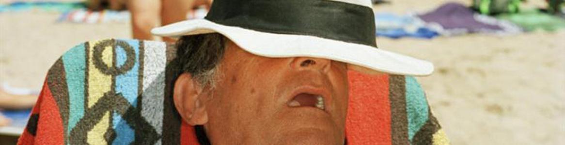 Hombre dormido y cubierto con sombrero en la playa