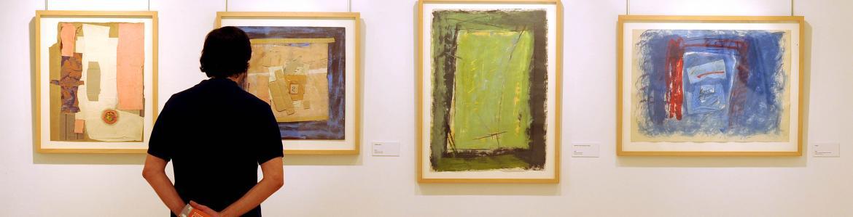 Hombre de pie observando varios cuadros abstractos de colores en la pared de una exposición