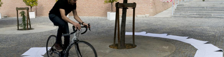Joven montando en bicicleta sobre un círculo hecho con papeles blancos