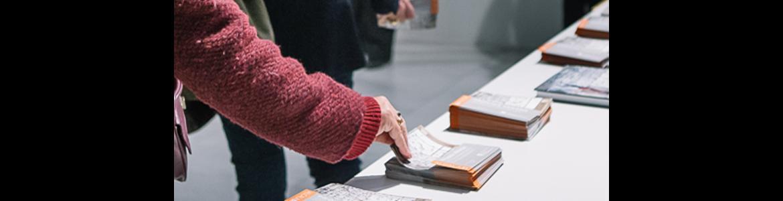 Mano cogiendo un folleto en una mesa blanca en un museo