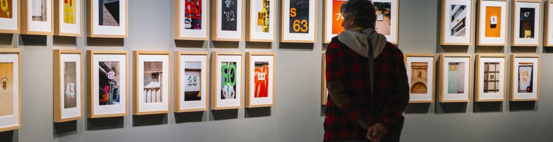 Hombre mirando una serie de fotografías con números en la Sala Canal