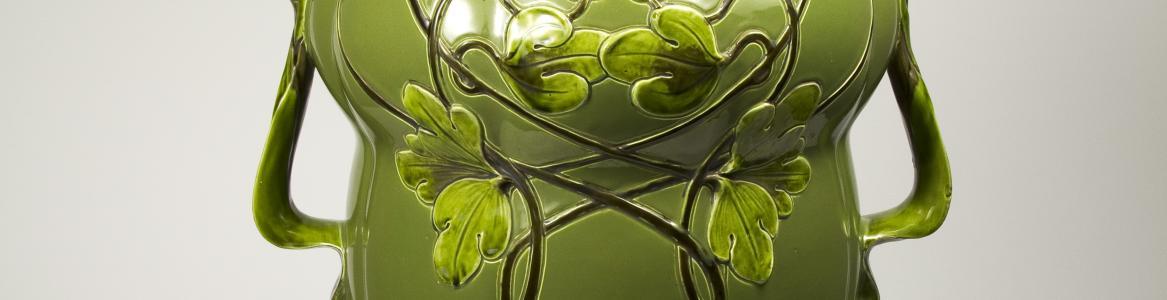 Jarrón antiguo de color verde con formas vegetales y decoración floral