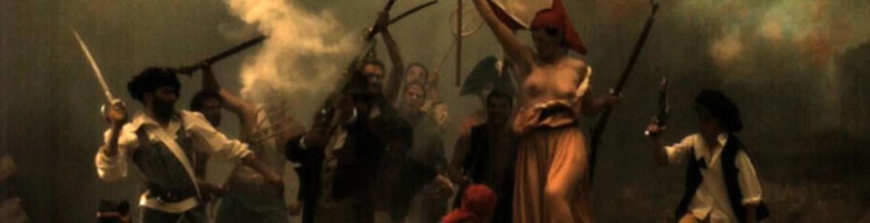 Fotografía en color con un grupo de personas que simulan estar en una batalla y cuyo personaje central, una mujer, con el pecho al descubierto alza la bandera de Francia