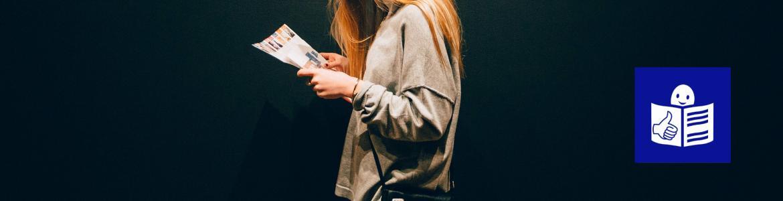 Mujer joven de perfil leyendo un folleto