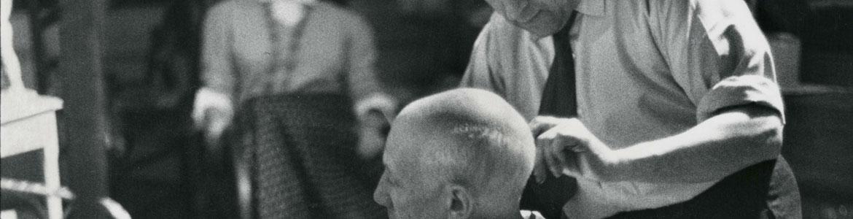 Fotografía en blanco y negro de David D. Duncan en la que aparece Picasso sentado mientras su barbero Eugenio Arias le corta el pelo