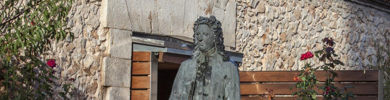 Fachada de un edificio de piedra con una estatua de un hombre del siglo 18