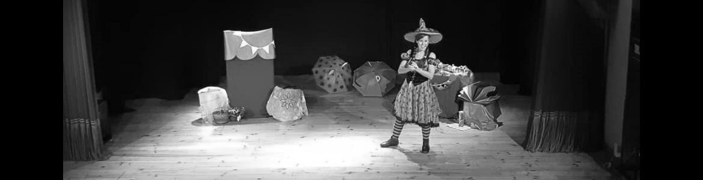 imagen en la que se ve a la cuentacuentos disfrazada de bruja en un escenario con muchos paraguas de colores