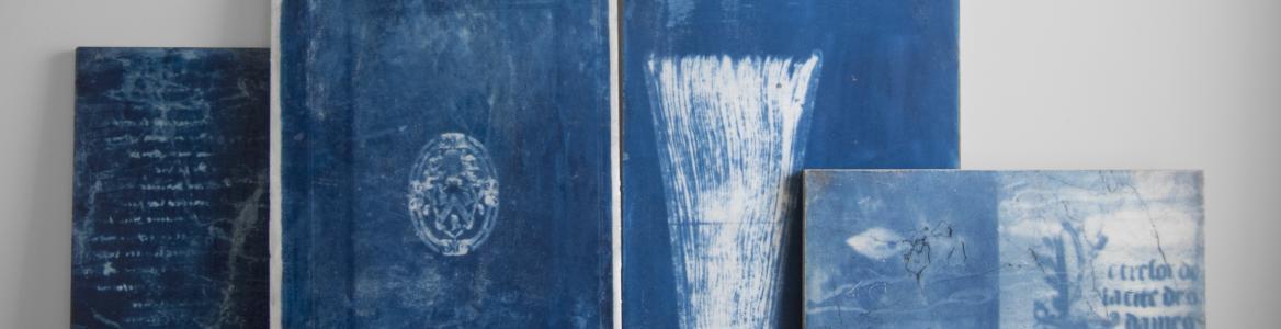 Lienzos azules con dibujos abstractos apoyados en el suelo