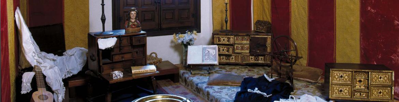 Habitación antigua con una tarima en el suelo, alfombras, tapices y muebles antiguos