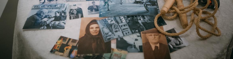 Mesa camilla con fotografías antiguas desordenadas sobre ella