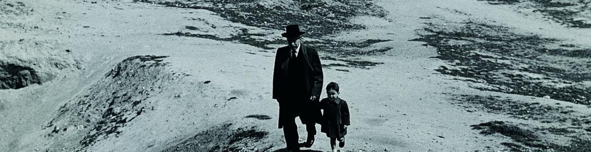 Fotografía en blanco y negro de un hombre y su pequeño nieto paseando por un descampado y, al fondo, una serie de edificios de la periferia de Madrid