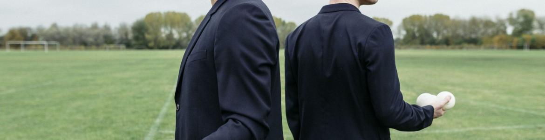 imagen en la que se ve a los dos interpretes dandose la espalda en un campo