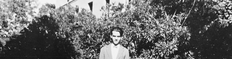 Fotografía de Lorca de pie, mirando a la cámara, en el jardín de la Residencia de Estudiantes