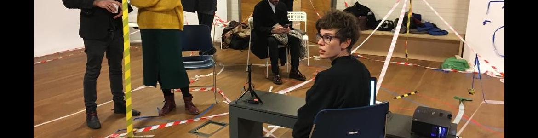 Instalación artística con cintas de seguridad rodeando todo el espacio y varias personas circulan entre ellas