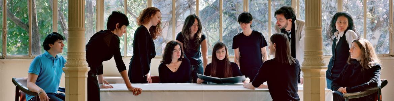Grupo de personas vestidas de negro en torno a una mesa