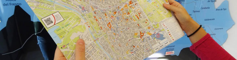 Usuaria de las oficinas de turismo observa un plano de la ciudad de Madrid